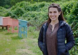 Emma Egstad (Bee and Bloom) with bee hives in the background